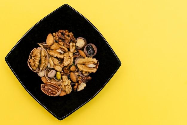 クルミ、ピスタチオ、ピーカン、アーモンド、ブラックのスクエアプレート。健康食品のコンセプトです。