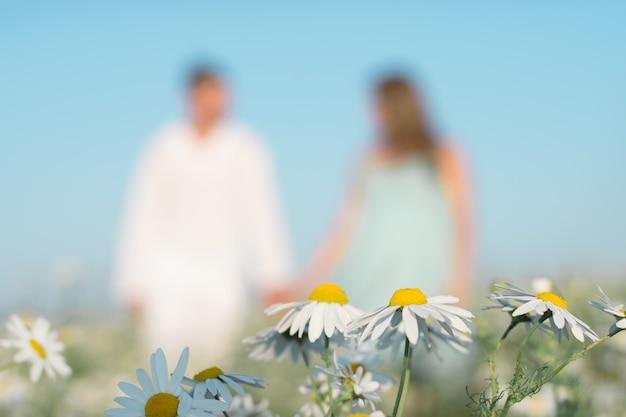 後ろに手を繋いでいるカップルと牧草地の鎮静にクローズアップ