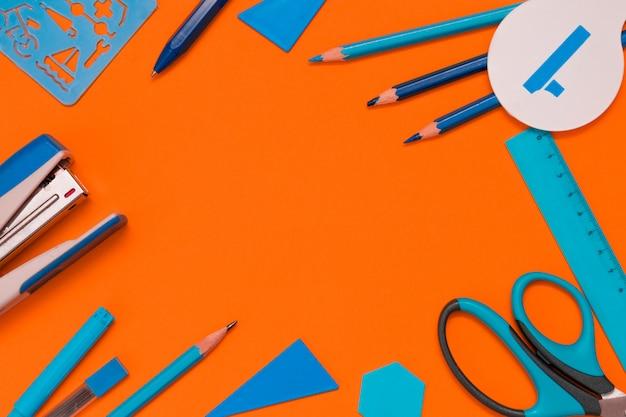 定規、色鉛筆、ペン、フェルトペン、はさみ、ホチキス、プラスチックの幾何学的要素。学校のコンセプトに戻るフラットが横たわっていた。
