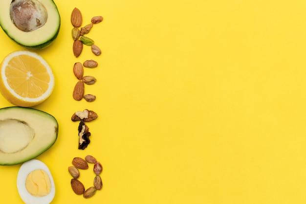 ナッツとアボカド、卵、レモン、ナッツのフレームからの碑文「ケト」。ケトン食の概念。