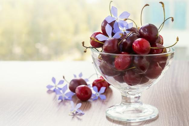 さくらんぼとテーブルの上の透明なガラスの花瓶に花。夏のコンセプト。
