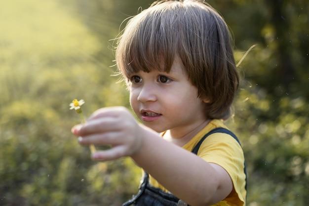 小さな花を与える金髪の少年