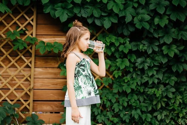 かわいい女の子は水を飲みます。サマータイム