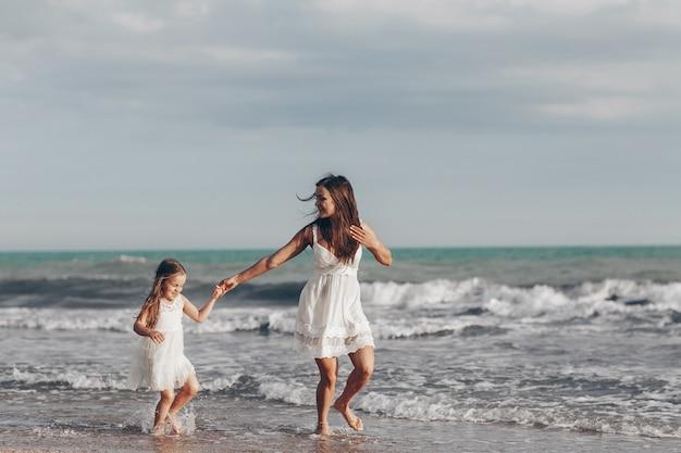 ビーチで晴れた日を楽しんで幸せな母と娘