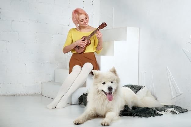 Молодая улыбающаяся женщина-девушка в юбке и блузке, играющая на гавайской гитаре, сидит на ступеньках с улыбкой на лице, а ее белая собака-самоедка лежит на ковре у ее ног.
