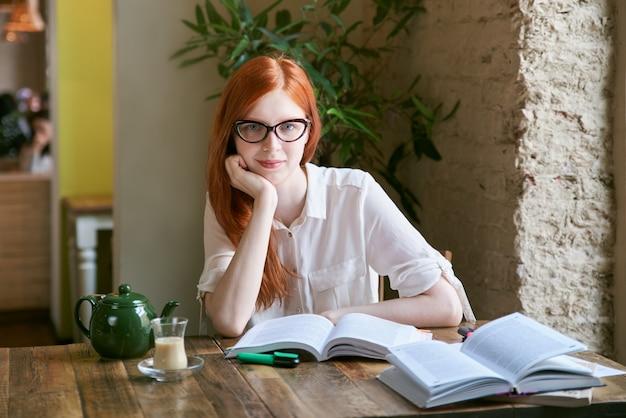 カフェでテーブルの上に卒業証書と研究作業を書く宿題をしている若い学生女性。長い赤髪、メガネ、白いブラウス