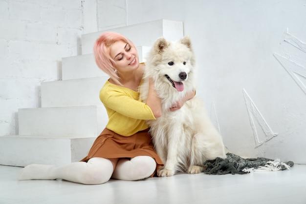 幸せな美しい少女と彼女の大きな白い犬が腕の中で喜んで座っています。美しい若い女性と彼女のペットは親友です。抱きしめ、遊んで、人生を楽しんでください。