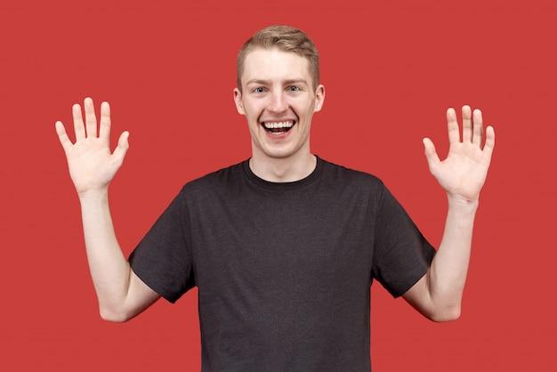 Радостный счастливый молодой человек поднимает руки в позе «сдачи» смеха и с удовольствием встречается с друзьями. концепция игривого поведения, энтузиазма и радости.