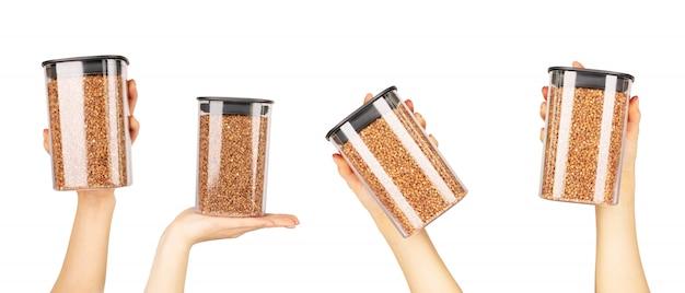 穀物を保存するためのプラスチック容器に入ったソバ粒。女性の手は、孤立した白地にそばの瓶を保持しています。適切な栄養のためのソバ粒。