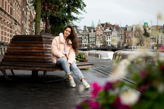 旧市街のベンチに座っている女の子。背景にはアムステルダムの美しい自然、運河、住宅があります。観光休暇。