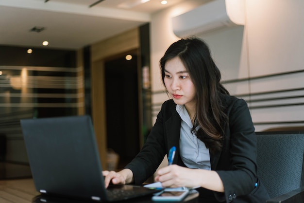 彼女のラップトップを使用して美しい若いアジア女性