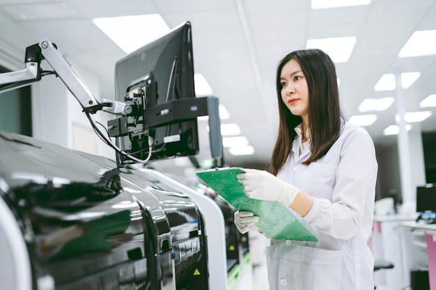 若い女性科学者が自動血液分析装置レポートの結果を記録