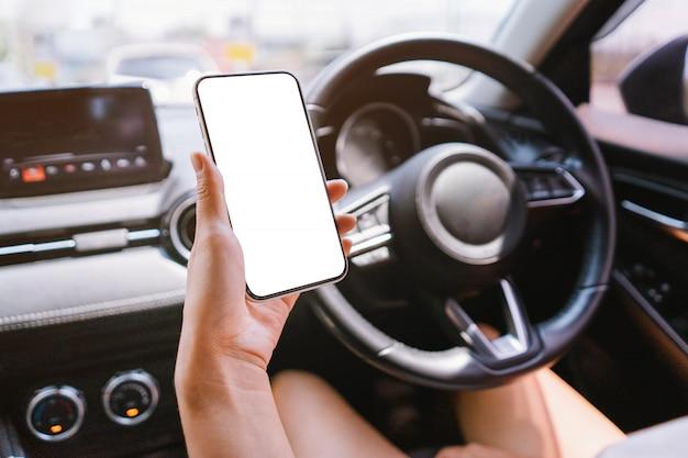 女性は車の中でモックアップ付きのスマートフォンを持っています。