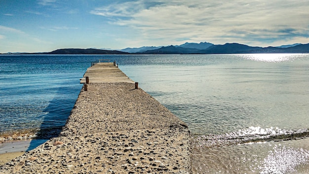 Старый маленький пирс протянулся на несколько метров по спокойным водам острова таволара в цветах сардинского моря
