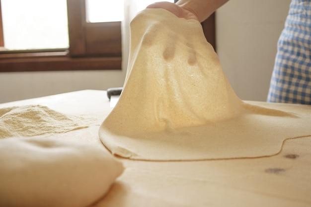Приготовление домашней свежей пасты: женская рука с подсветкой демонстрирует прозрачность только что раскатанного теста
