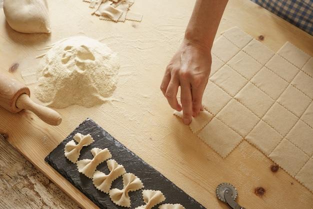 Процесс приготовления домашней пасты фарфалле. повар формует тесто на деревянной разделочной доске