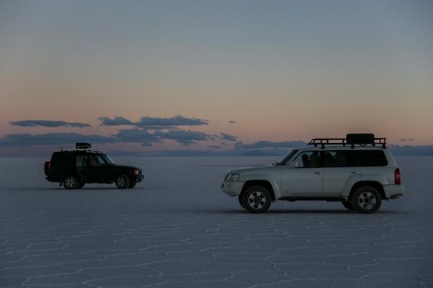 雪の中で夕日と地形の車