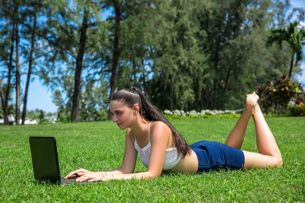 公園の芝生の上に座っているラップトップを持つ少女