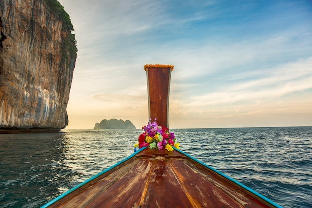 熱帯の島の夕暮れ時の伝統的なロングテールボート