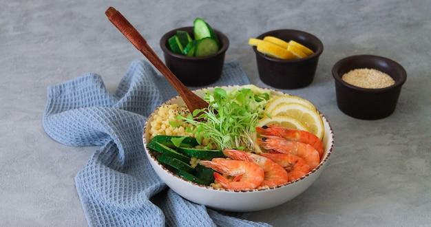 Сбалансированный и полезный салат «чаша будды» с морепродуктами, органическими овощами и кус-кусом на каменном фоне