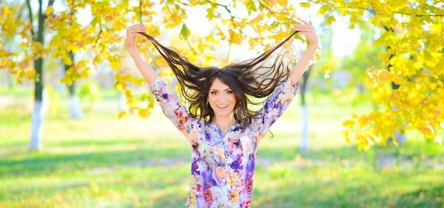 Портрет веселый смех молодая брюнетка женщина с желтыми осенними листьями. леди играет со своими волосами
