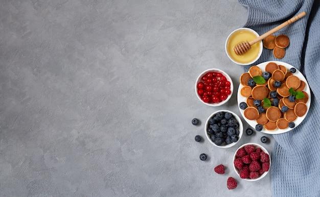 蜂蜜、スレート背景上面に新鮮な果実とパンケーキシリアルまたはミニパンケーキ。トレンディなデザートと健康的な朝食。