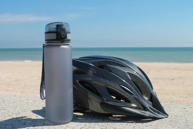 Серый велосипедный шлем и серая бутылка с водой - велосипедные аксессуары на фоне океана