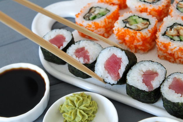 Свежеприготовленные суши. маки с тунцом и калифорнии крупным планом. палочки для еды принимают порцию суши-роллов на стол ресторана. есть японскую еду
