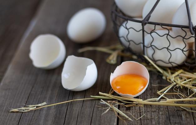 Свежие яйца фермы с желтком в яичной скорлупе на деревянный стол