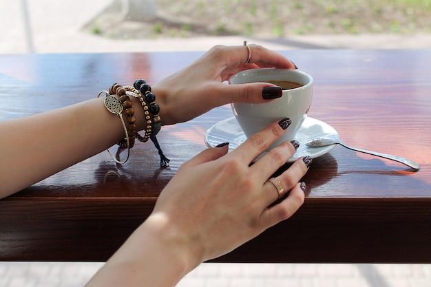 朝食のためのコーヒーのカップを保持している女性