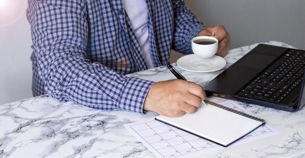 ノートパソコン、メモ帳、大理石の机に座っているコーヒーのカップを持つ青年実業家の側面図