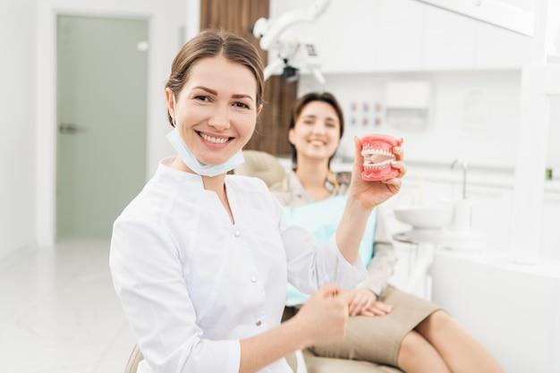 歯科医院で入れ歯を持つ女性歯科医