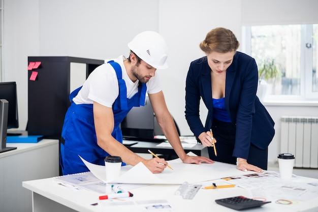 Два архитектора, мужчина и женщина, работают над проектом строительства