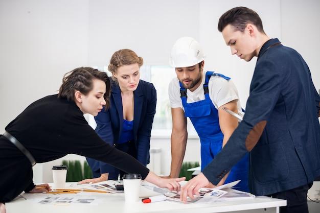 Команда из четырех инженеров обсуждает проект в офисе