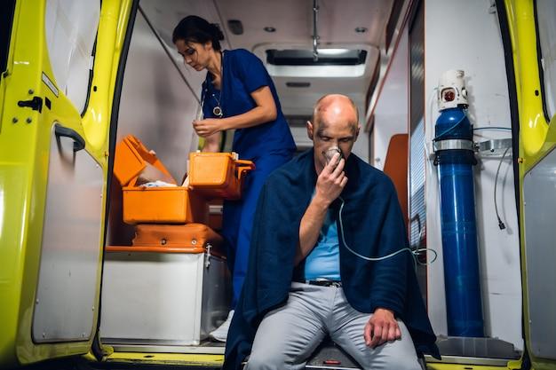 救急車、若い看護婦が患者に応急処置をするために彼女の医療キットをチェックしています
