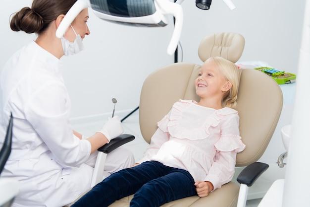 クリニックでの歯科治療後に彼女の完璧な笑顔を見せて満足している小さな歯科医の患者