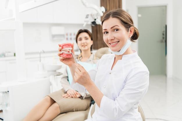Врач держит искусственную челюсть с помощью ортодонтического аппарата