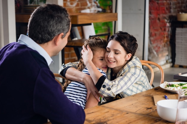 家族全員でダイニングテーブルに座っている娘を抱き締める母親
