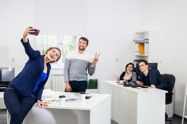 Время селфи. офисные работники, принимающие селфи на работе