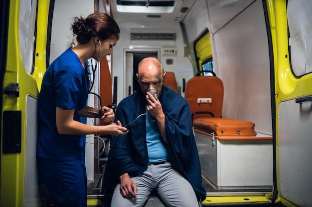 負傷した男性の世話をする当番の若い女性救急救命士