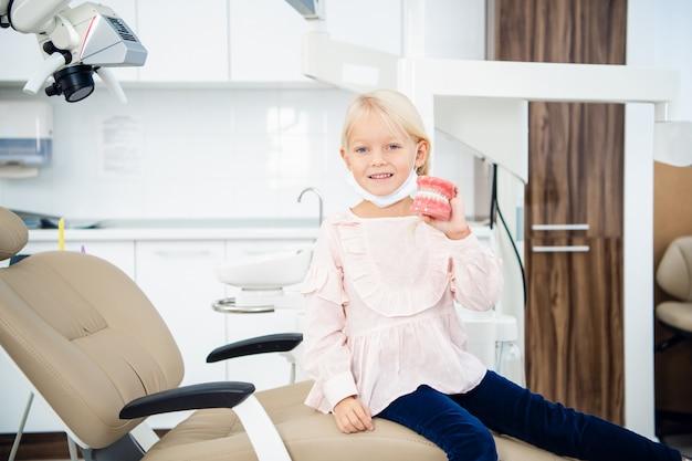Маленькая девочка держит в руке искусственные зубные протезы в стоматологическом кабинете