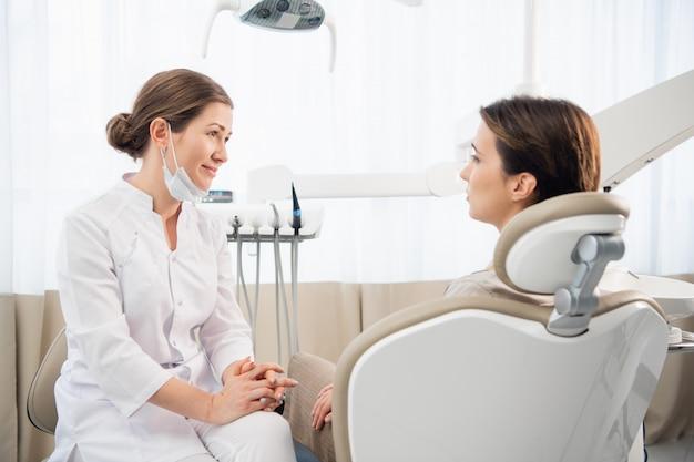 Портрет крупного плана женского дантиста советуя с ее пациентом. профилактическая медицинская ежегодная проверка. положительное выражение лица
