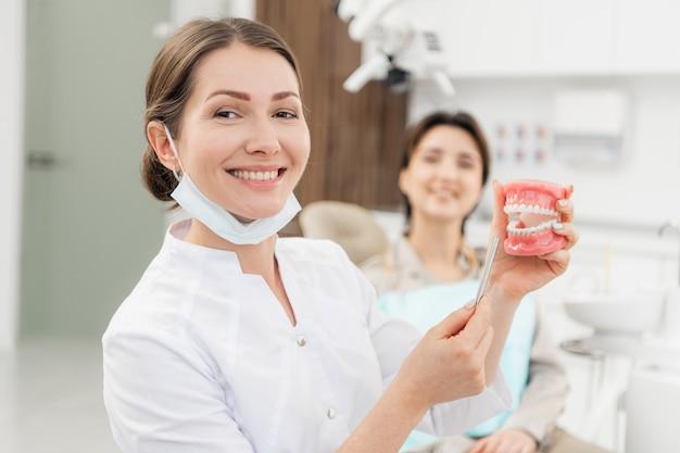 Портрет доктора, держащего искусственную челюсть с помощью ортодонтического аппарата