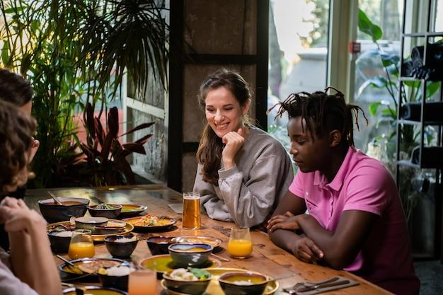 Многокультурная группа студентов в кафе, едят азиатскую еду, пьют коктейли, общаются в чате