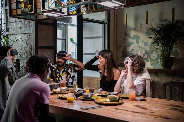 Позитивные друзья со своими смартфонами на лбу сидят за обеденным столом и пытаются угадать слово, написанное на их дисплеях