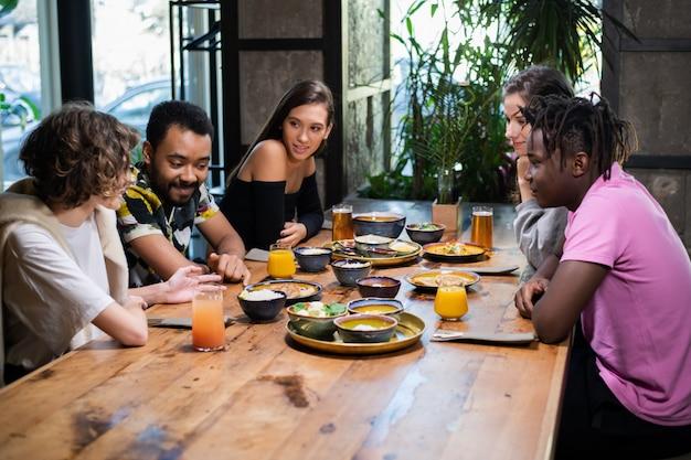 Группа друзей, сидя и перекусить в кафе