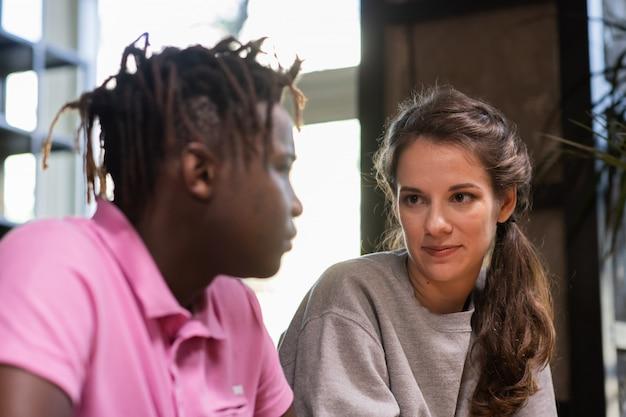Молодые зарубежные друзья сидят рядом и разговаривают