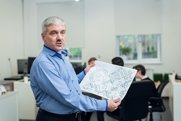 Седой мужчина проводит презентацию перед аудиторией с техническими чертежами