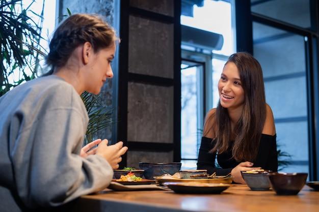 Две счастливые девушки едят и веселятся во время общения в кафе