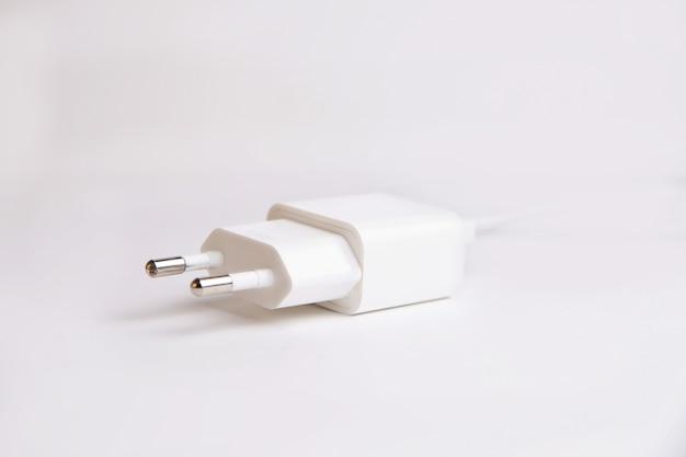 白い壁にスマートフォン用の白い充電器アダプター